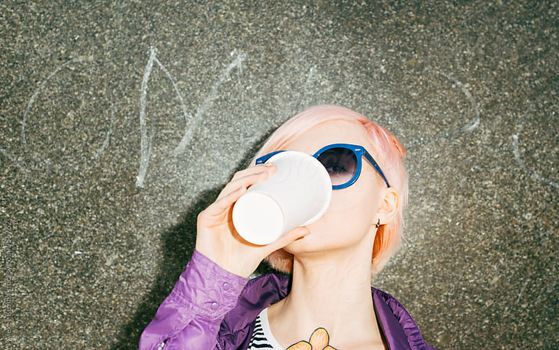 cool young woman with pink hair drinking a tea on the street by Vesna for Stocksy United