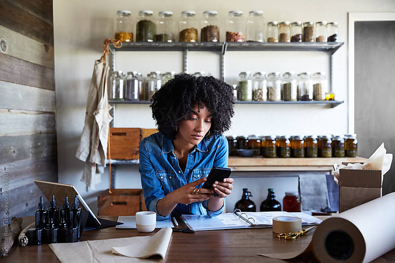 Millennial African American Woman businesswoman texting in her skincare studio by Trinette Reed for Stocksy United