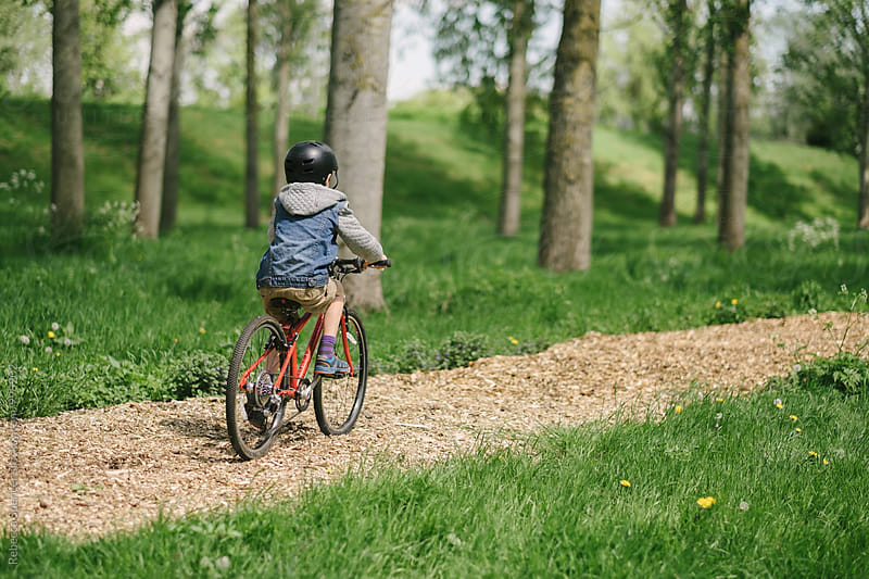 Child rides his bike at speed along a path in the woods by Rebecca Spencer for Stocksy United
