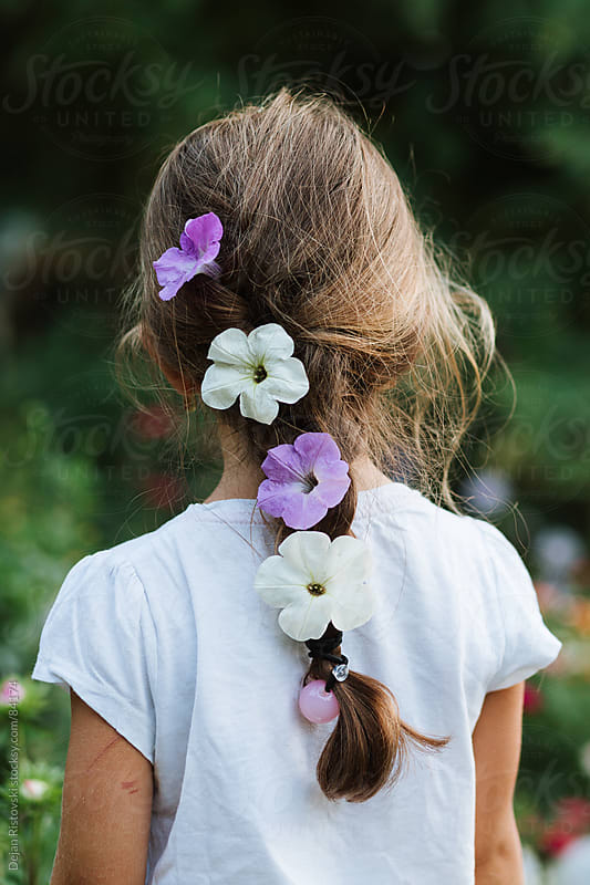 Little girl's hair with white and purple flowers by Dejan Ristovski for Stocksy United
