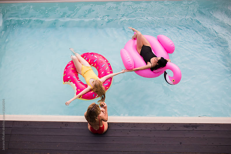 Female friends having fun in the pool by Jovana Rikalo for Stocksy United
