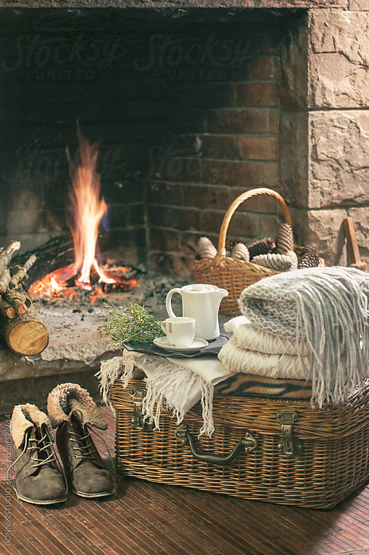 Cozy home. Still life of woman's boots, blankets and kettle in front fireplace. by BONNINSTUDIO for Stocksy United