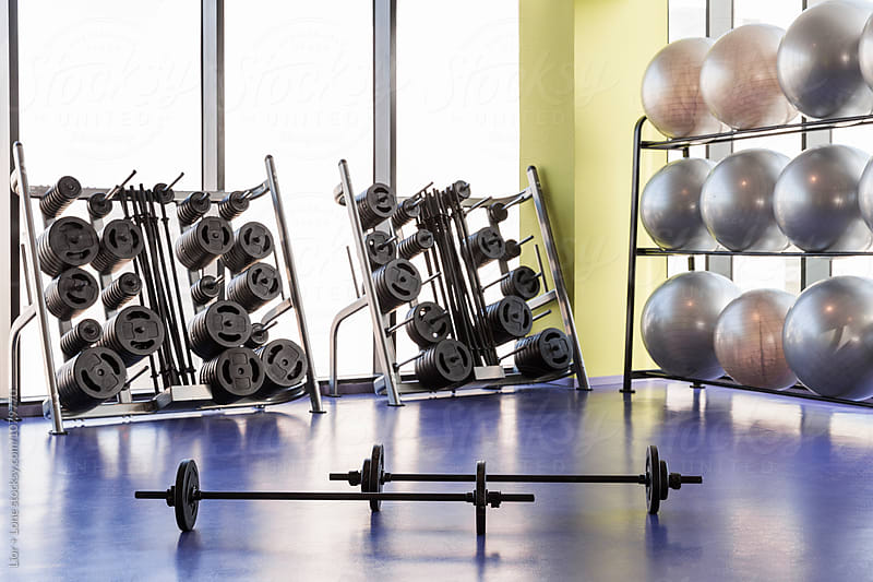 Barbells on the floor of an open space studio gym by Lior + Lone for Stocksy United