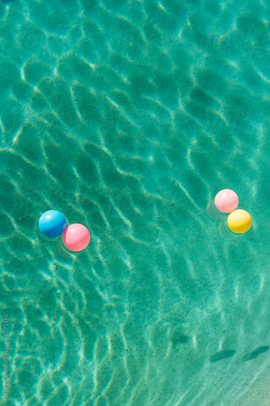 coloured balls floating in a swimming pool by Gillian Vann for Stocksy United