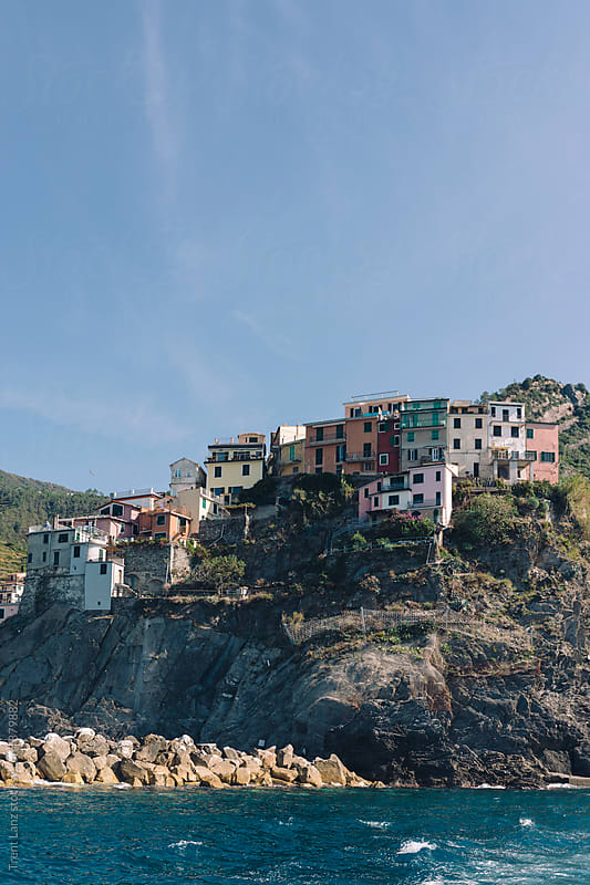 Colorful fishing village buildings on cliff from boat by Trent Lanz for Stocksy United