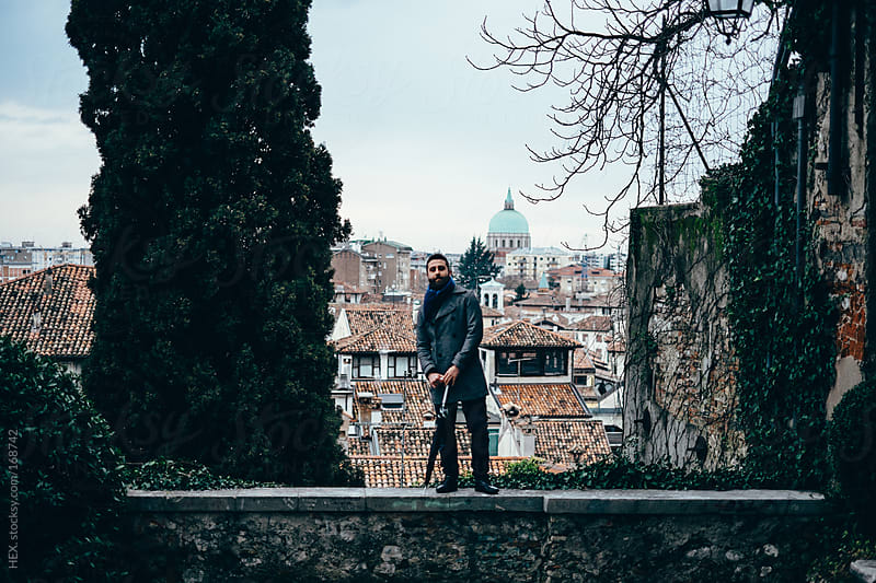 Handsome Man Standing On a Wall In Front Of an Italian City by HEX. for Stocksy United
