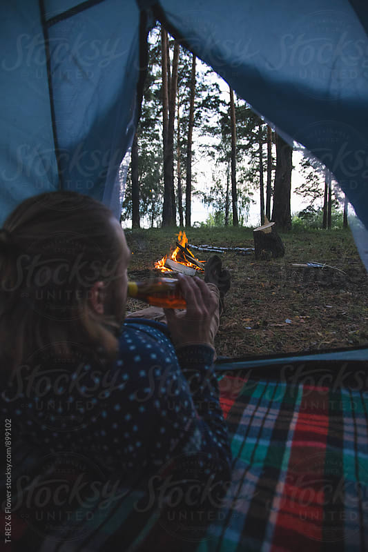 Man in tent drinking beer and looking at campfire by Danil Nevsky for Stocksy United