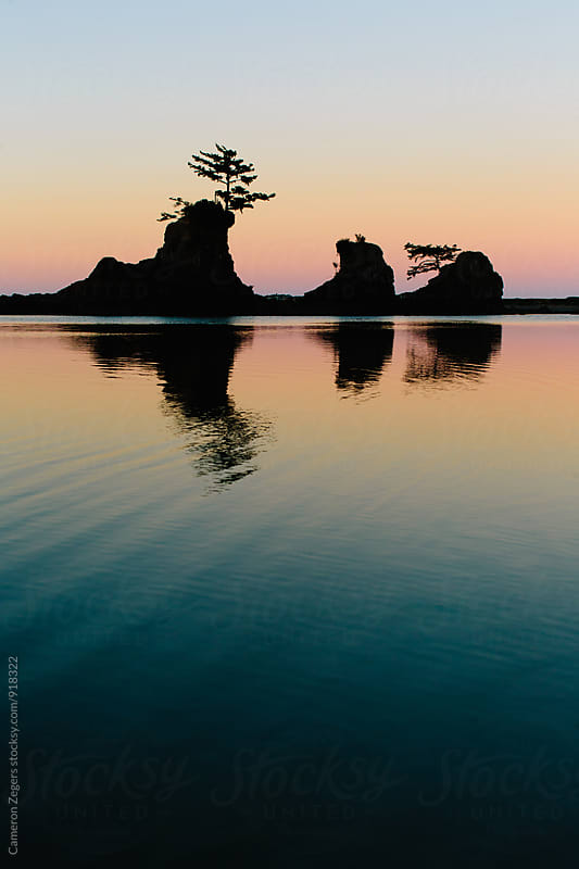 silhouetted rocks in bay at sunrise by Cameron Zegers for Stocksy United