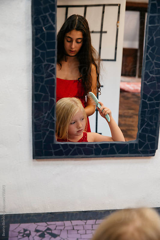 Two sisters in front of the mirror getting ready for the festivities by Beatrix Boros for Stocksy United