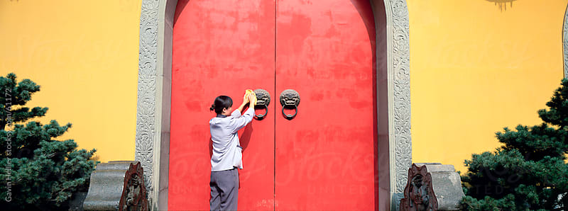 Woman cleaning the door of the Jade Buddha Temple, Shanghai, China by Gavin Hellier for Stocksy United