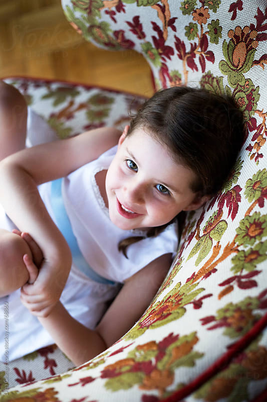 Girl sitting in colorful rounded back chair looking up and smiling  by Dina Giangregorio for Stocksy United