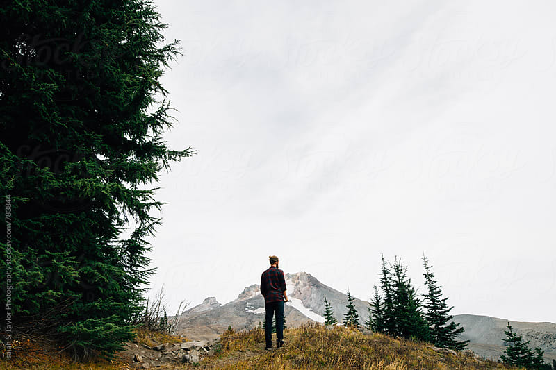 Man standing in front of mountain by Isaiah & Taylor Photography for Stocksy United