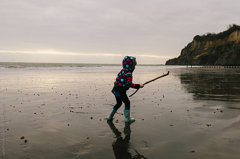 Little girl runs with a stick on a wet wintry beach in the morning. by Julia Forsman for Stocksy United