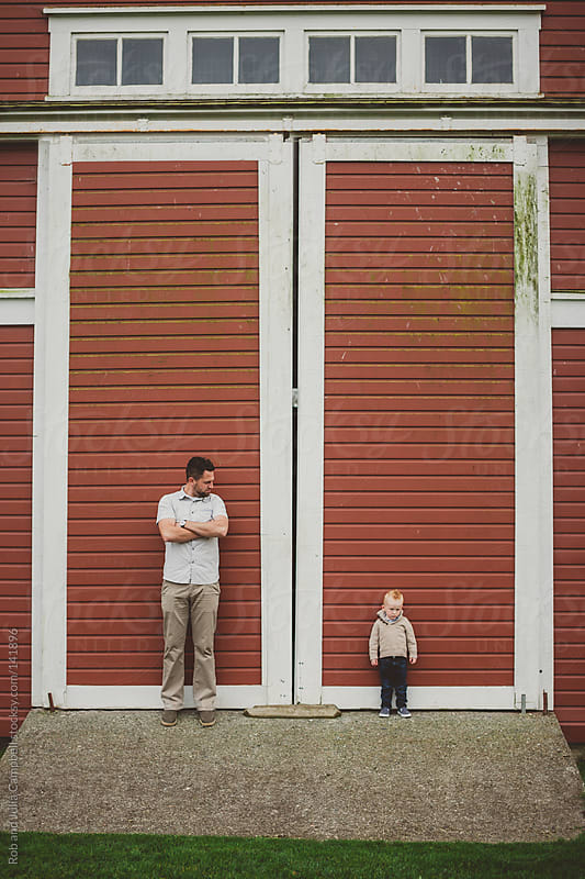 Dad and young son standing in front of red barn door of red barn by Rob and Julia Campbell for Stocksy United