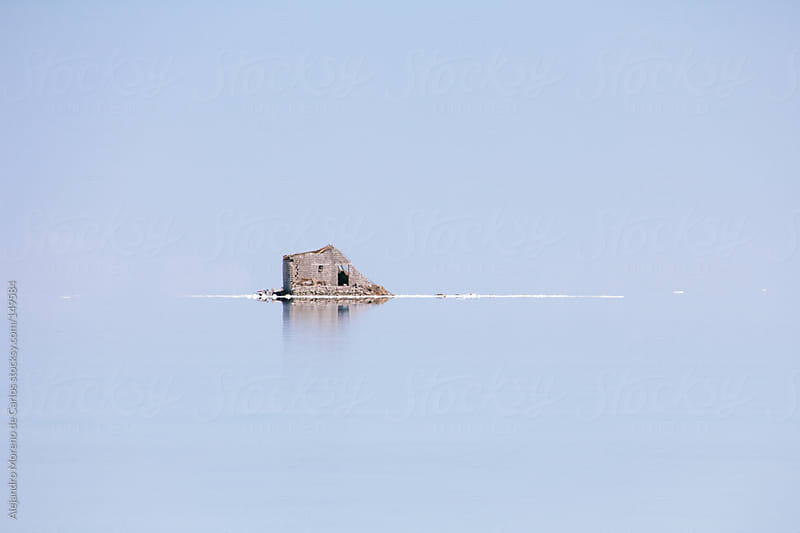Lonely ruin house on empty blue water. Uyuni salt flat by Alejandro Moreno de Carlos for Stocksy United