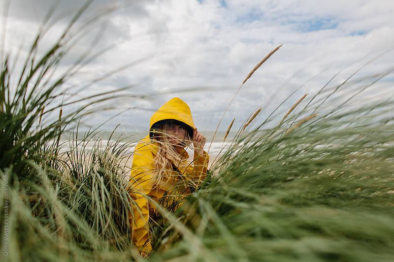 Woman sitting between high grass on a windy beach wearing a yellow raincoat by Denni Van Huis for Stocksy United