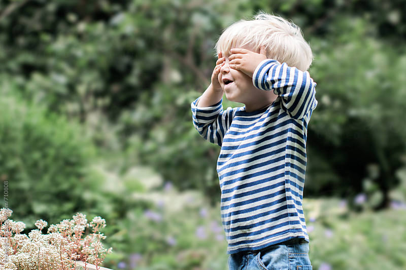 Excited toddler playing hide and seek by Per Swantesson for Stocksy United