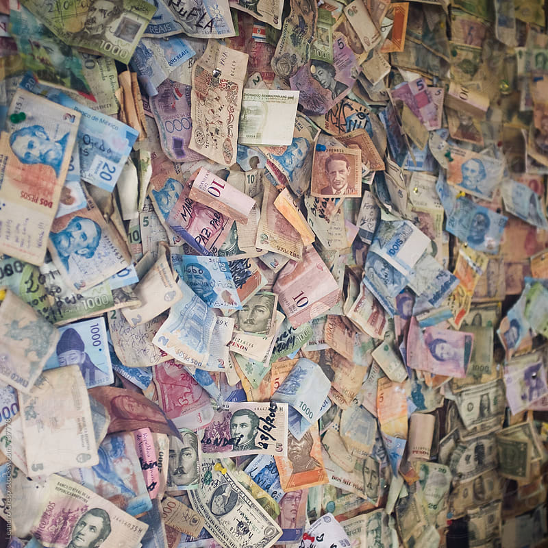 A wall full of money from all over the world by Leandro Crespi for Stocksy United