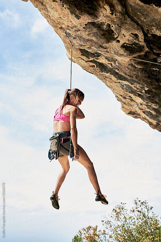 Brunette climber descending on rope by Guille Faingold for Stocksy United