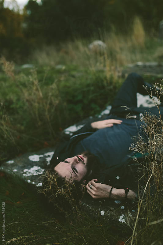 Man Lay Down on a Gravestone in a Cemitery by HEX. for Stocksy United