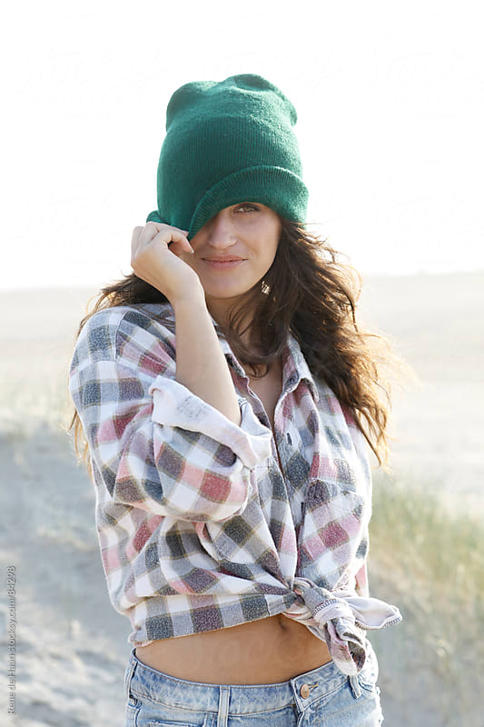 girl with green hat on beach by Rene de Haan for Stocksy United
