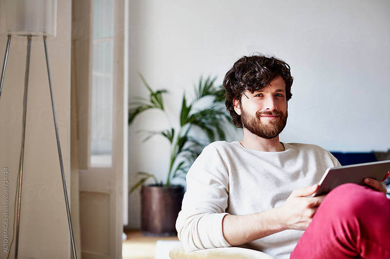 Happy Man Holding Digital Tablet At Home by ALTO IMAGES for Stocksy United