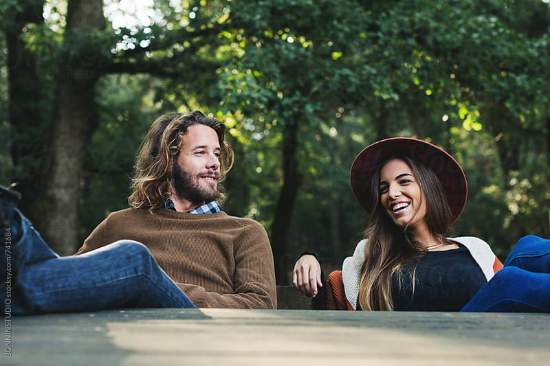 Portrait of a couple smiling sitting on a bench in the forest. by BONNINSTUDIO for Stocksy United