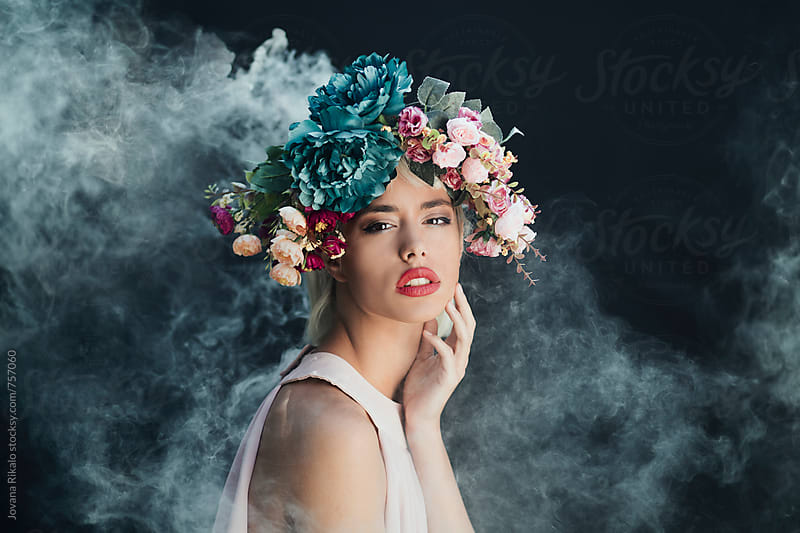 Portrait of a beautiful young woman in a smoke by Jovana Rikalo for Stocksy United