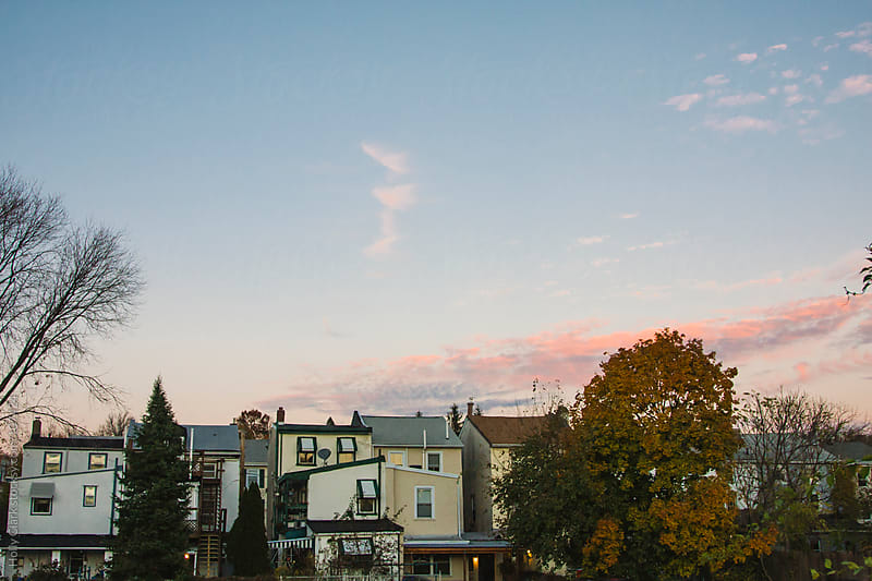 City neighborhood at sunset in fall. by Holly Clark for Stocksy United