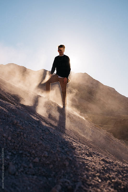 young man standing tall with sunlight at his back and dust flying around him by Jesse Morrow for Stocksy United