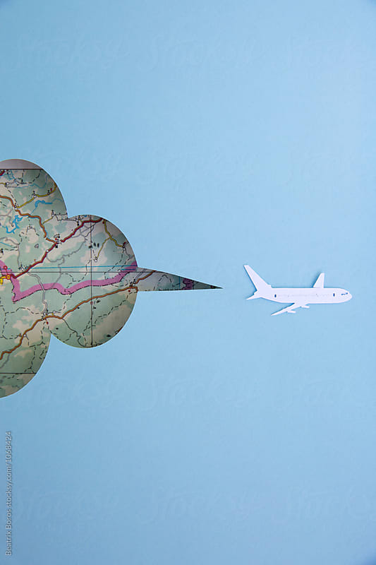 Paper airplane flying in front of  a map by Beatrix Boros for Stocksy United