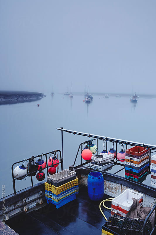Fishing boat moored in the harbour in fog at dawn. Wells-next-the-sea, Norfolk, UK. by Liam Grant for Stocksy United