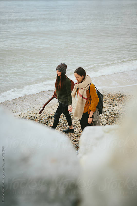 Two female friends walking on the beach in autumn by Good Vibrations Images for Stocksy United