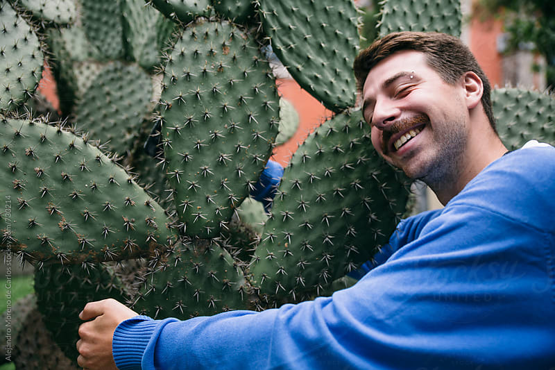 Young man happily hugging a cactus by Alejandro Moreno de Carlos for Stocksy United