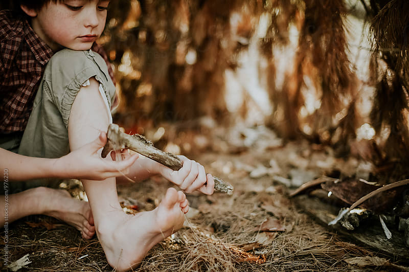Boy plays with sticks in the dirt by Michelle Gardella for Stocksy United