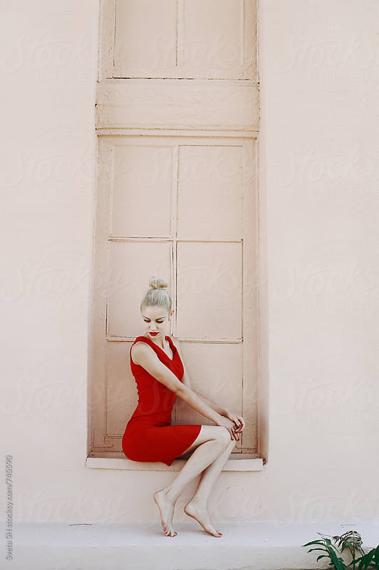 Blonde girl in a red dress by Sveta SH for Stocksy United