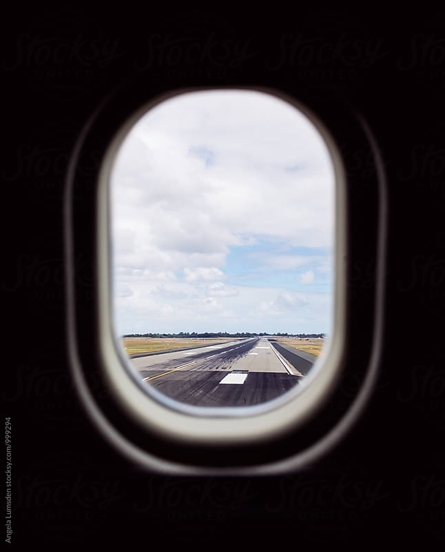 A view of a runway out an airplane window by Angela Lumsden for Stocksy United