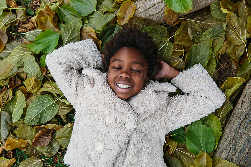 African American Girl Playing in Leaf Pile by Raymond Forbes LLC for Stocksy United