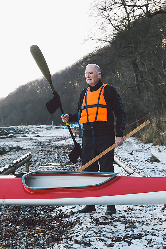 Portrait of senior man holding paddle by Lior + Lone for Stocksy United
