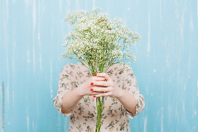 Woman hiding her face with Paniculata flowers. by BONNINSTUDIO for Stocksy United