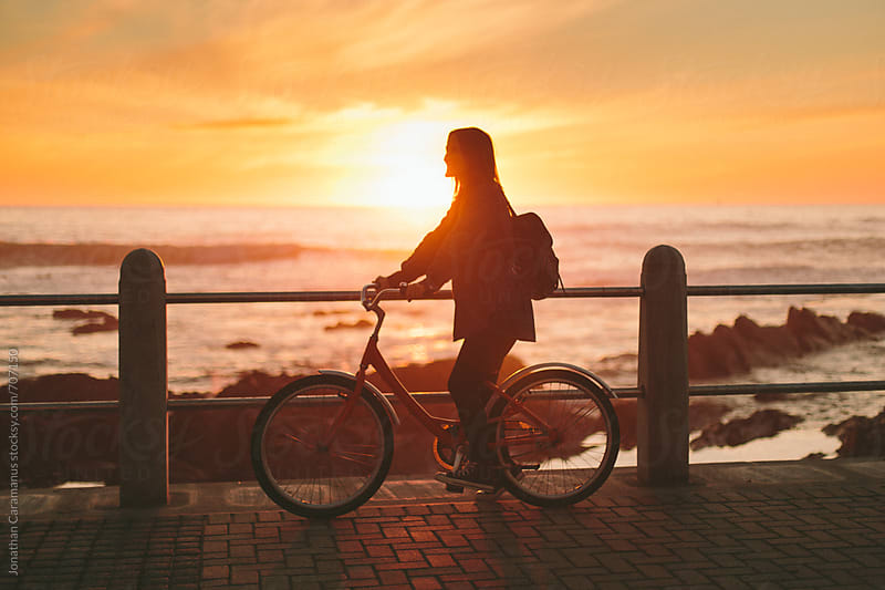 Beautiful girl on bicycle at sunrise or sunset overlooking the ocean by Jonathan Caramanus for Stocksy United