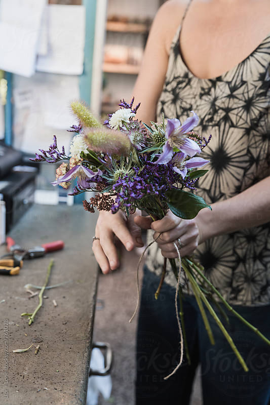 Woman's hands arranging a bouquet of purple flowers by Lior + Lone for Stocksy United