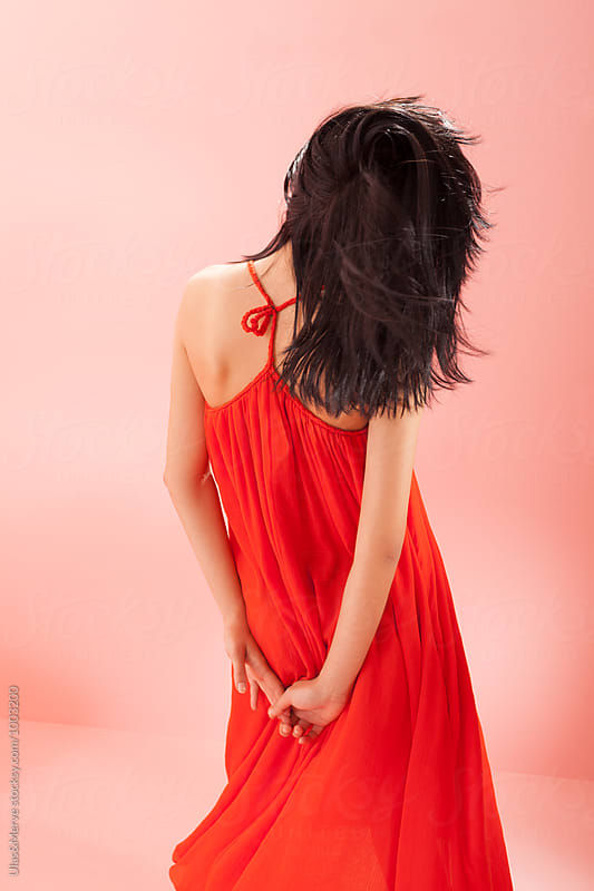 back of young brunette with a long red dress by Ulaş and Merve for Stocksy United