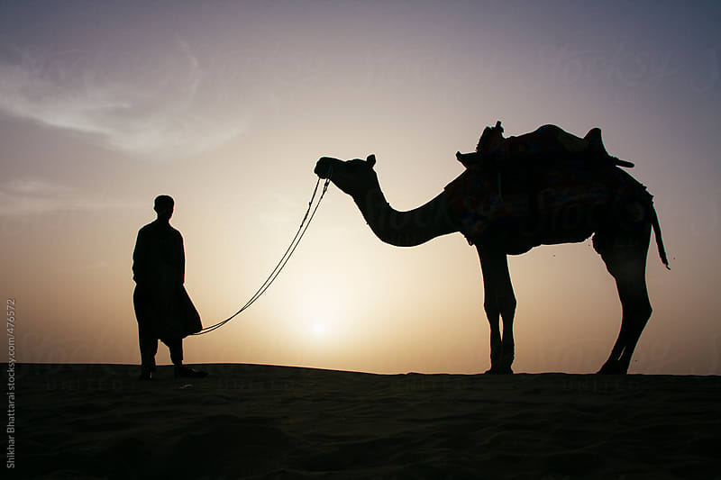 A silhouette of a young camel herder in the desert of Rajasthan, India. by Shikhar Bhattarai for Stocksy United