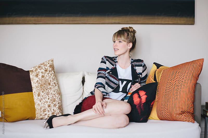 A beautiful blonde on a sofa in her living room by Ania Boniecka for Stocksy United