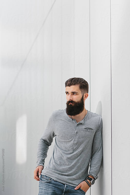 Handsome young man leaning against a gray wall by Amir Kaljikovic for Stocksy United