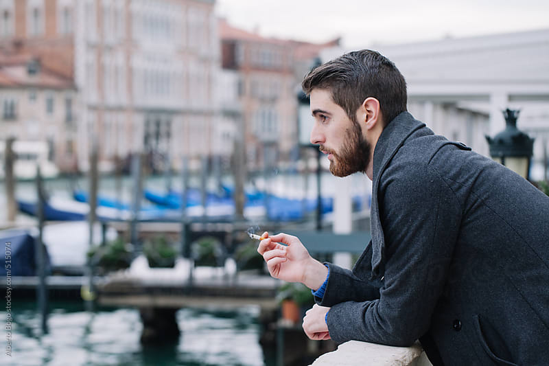 Portrait of a stylish man outdoors with cigarette by Alberto Bogo for Stocksy United