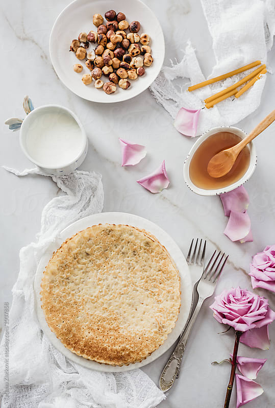 Crepes with honey, hazelnut and milk by Tatjana Ristanic for Stocksy United