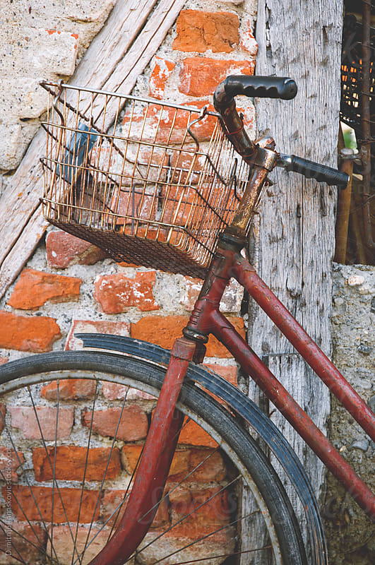 Old brown bicycle in front of the brick wall by Dimitrije Tanaskovic for Stocksy United