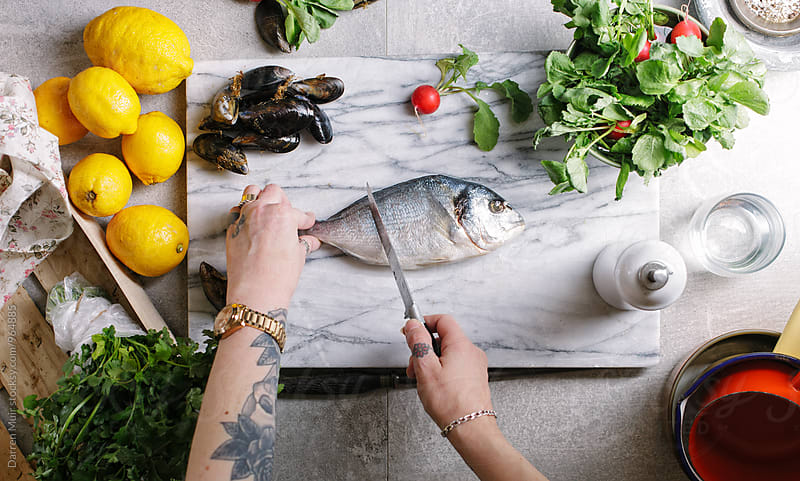 Woman preparing seabream and mussels for cooking on her kitchen table. by Darren Muir for Stocksy United